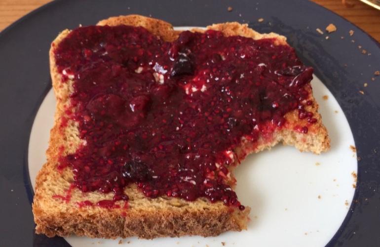 Ein Teller mit einem angebissenen Toast, beschmiert mit Chea-Marmelade