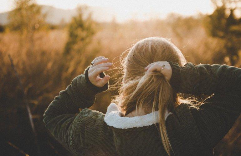 Eine Frau bindet sich die Haare zusammen