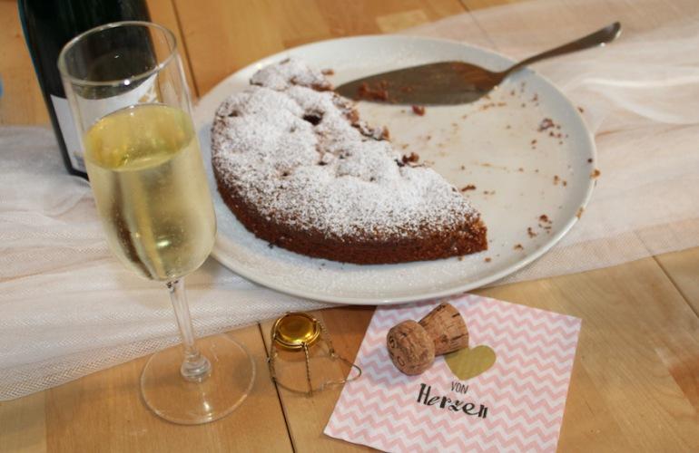 Ein Glas Sekt mit einem halben Schokoladenkuchen und einem Sektkorken