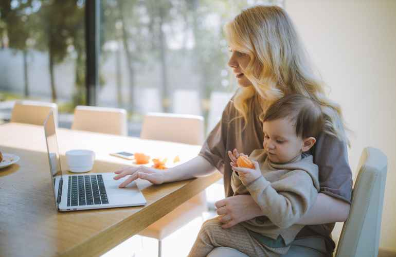 Frau, die ihr Baby trägt und an einem Laptop arbeitet