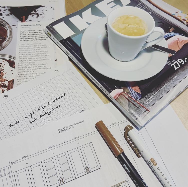 Eine Espressotasse steht auf einem Möbelkatalog. Daneben liegen Notizen für eine Küchenplanung