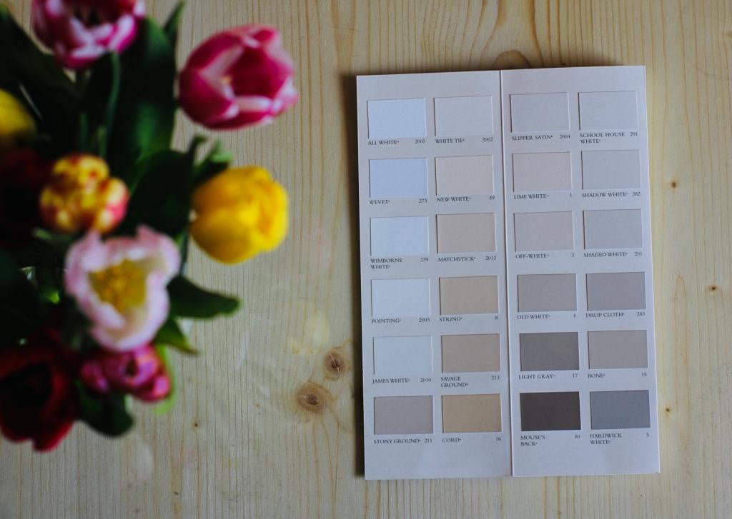 Das Bild zeigt mehrere bunte Tulpen sowie eine aufgeschlagene Farbpalette eines britischen Herstellers