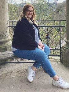 Frau posiert in einer Rotunde mit Blick auf eine Brücke