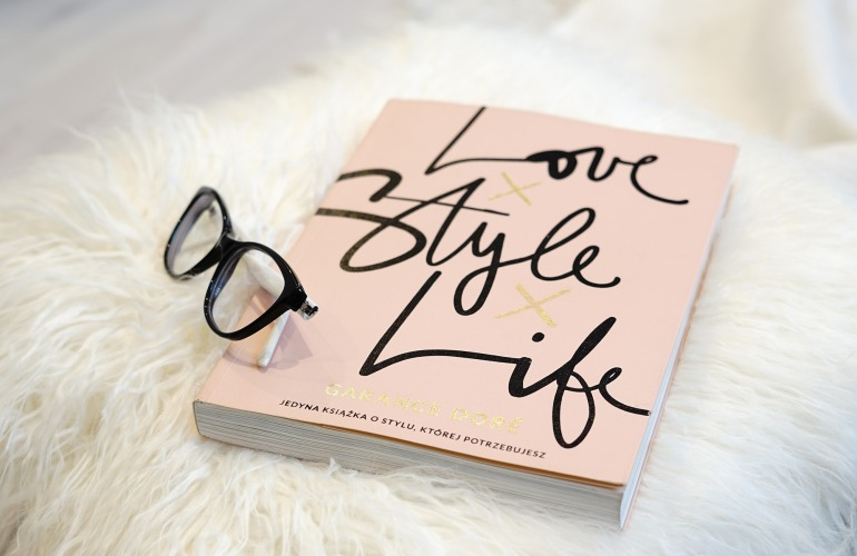 Ein Buch mit dem Titel 'Love Style Life' liegt auf einem Schaffellteppich, daneben liegt eine Brille
