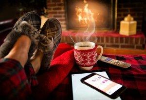 Neben ein Paar mit kuscheligen Hausschuhen bekleideten Füßen steht eine dampfende Tasse Tee. Im Hintergrund brennt ein Kaminfeuer.