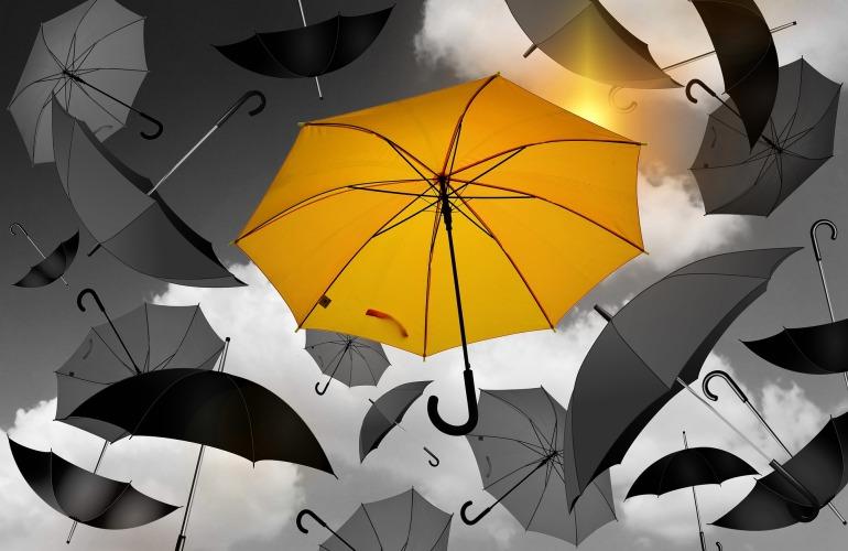 Ein einziger gelber Regenschirm fällt zusammen mit mehrere grauen Regenschirmen vom Himmel.
