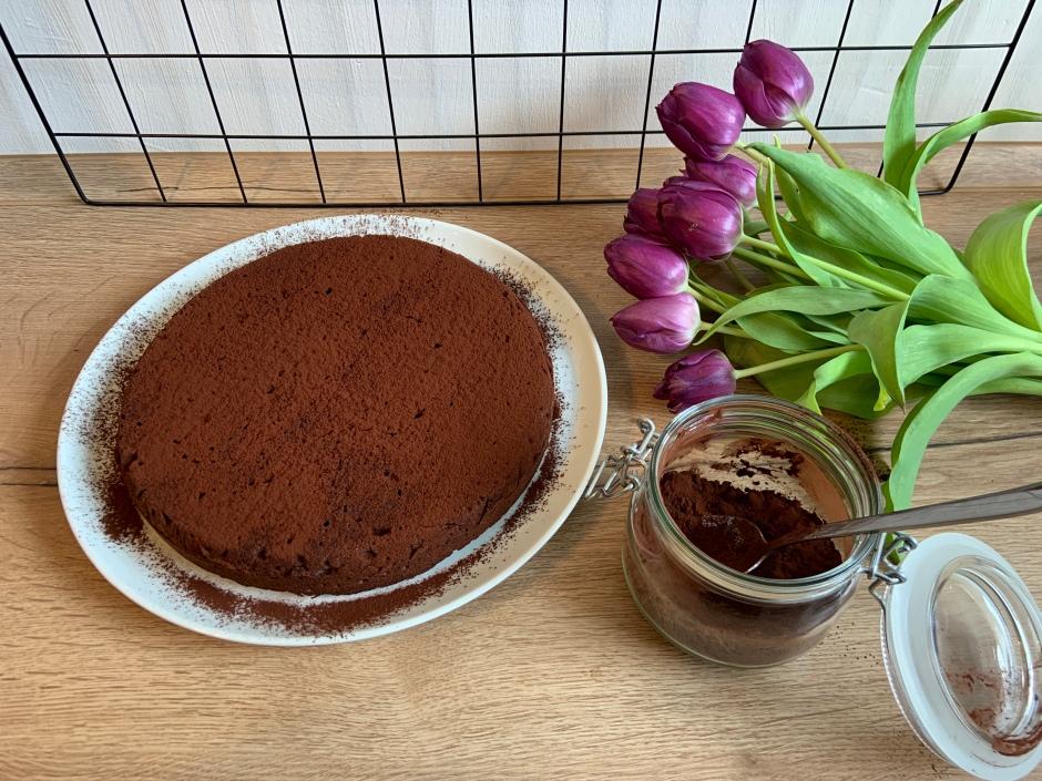 Schokoladenkuchen mit Tulpen und einem Einmachglas mit Kakao