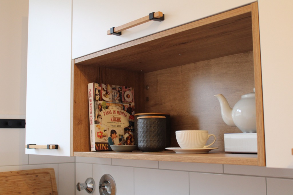 """Ein offenes Küchenregal mit Teekanne, Teetasse und einem Kochbuch mit dem Titel """"Paris in meiner Küche"""""""