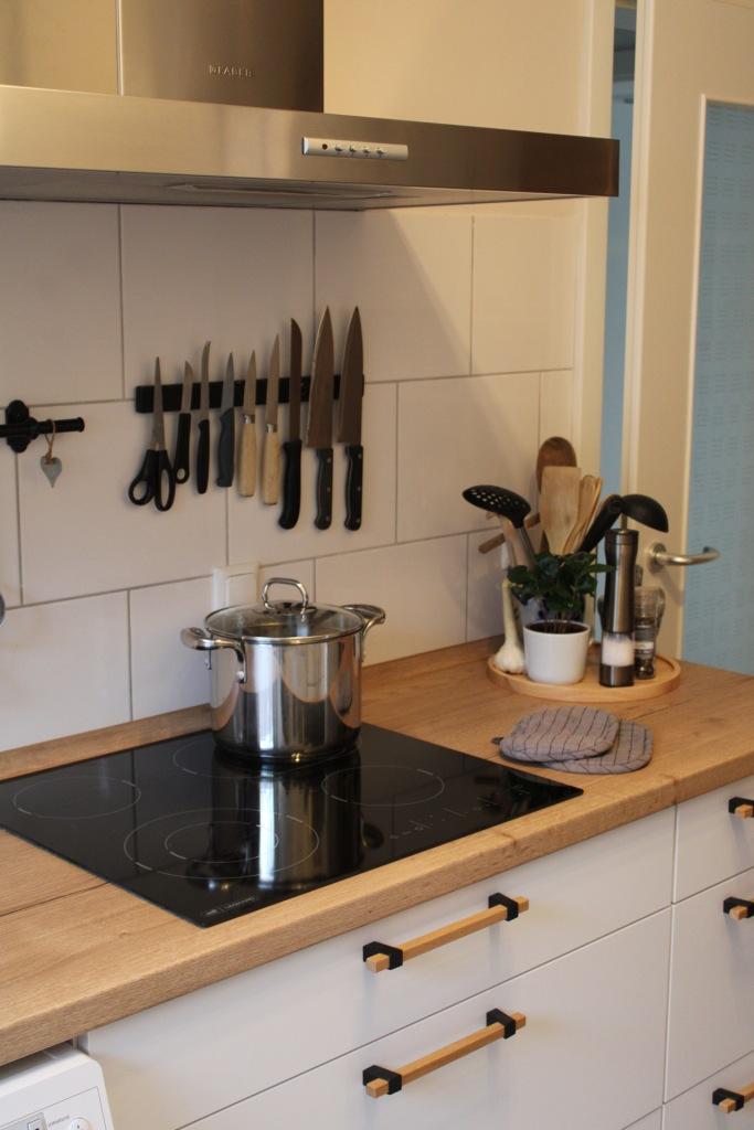 Eine Küchenzeile mit Herdplatte, Topf und Küchenutensilien.