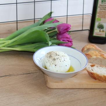 Das Bild zeigt eine Schale mit Mozzarella, daneben aufgeschnittenes Baguette sowie einen Strauß Tulpen