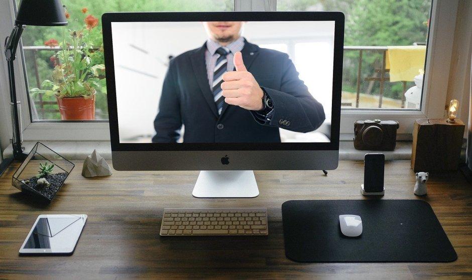 Das Bild zeigt einen Mann mit gehobenem Daumen auf dem Bildschirm eines iMacs.
