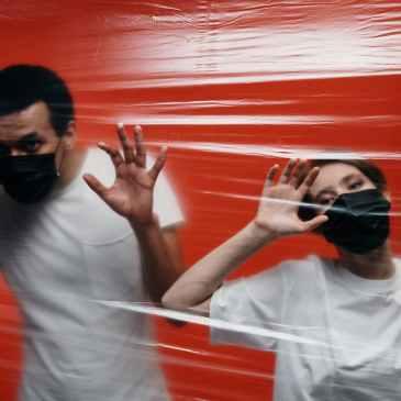 Zwei Personen mit Mund-Nasen-Schutz stehen hinter einer Wand aus Folie