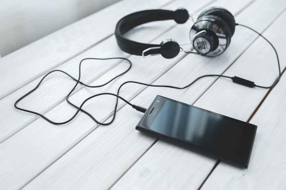 Ein Handy mit angesteckten Kopfhörern liegt auf einem Tisch